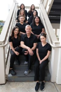Photo of Dr. Darnell dental team sitting together on stairs at dentist office in Hollister, CA