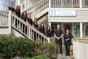 Darnell dental team standing together in front of dentist office in Hollister, CA